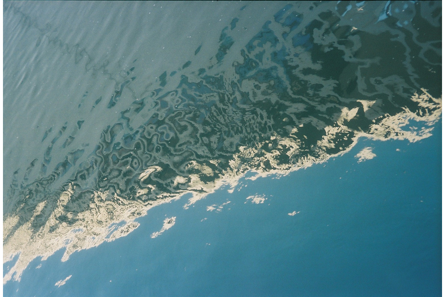 Photograph of water, closeup, part choppy and green, part placid and blue