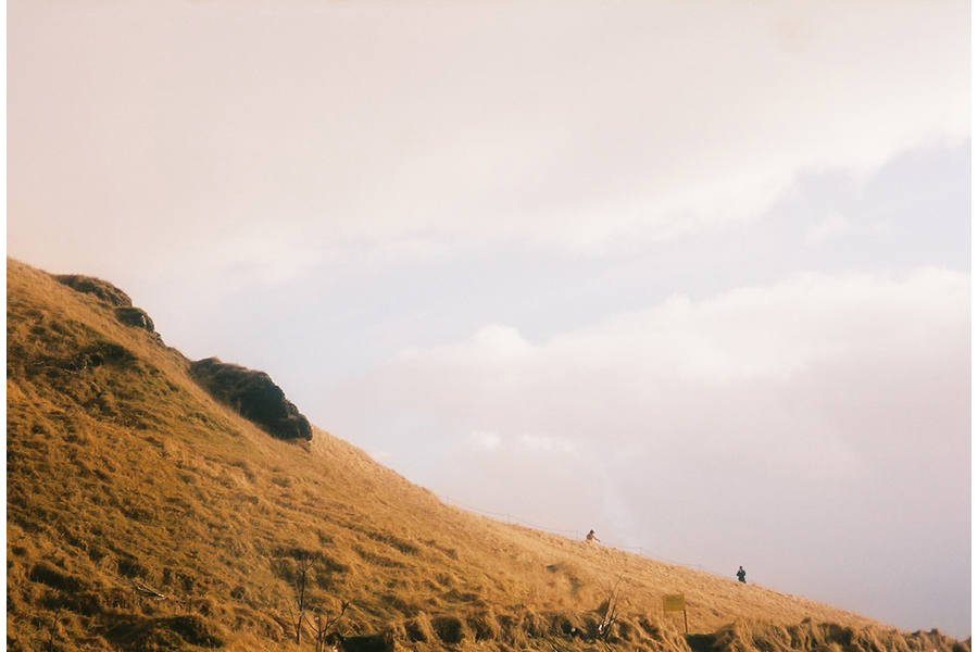 A photograph of a tawny-grassed slope against a pinkish-white sky. Far in the distance, two figures appear a few yards apart, near the base of the slope.