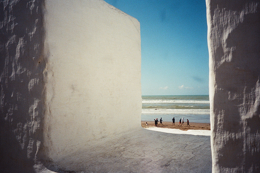 A view onto a beach through white cement walls. A group of people stand near the water's edge, a clear, cerulean sky in the background