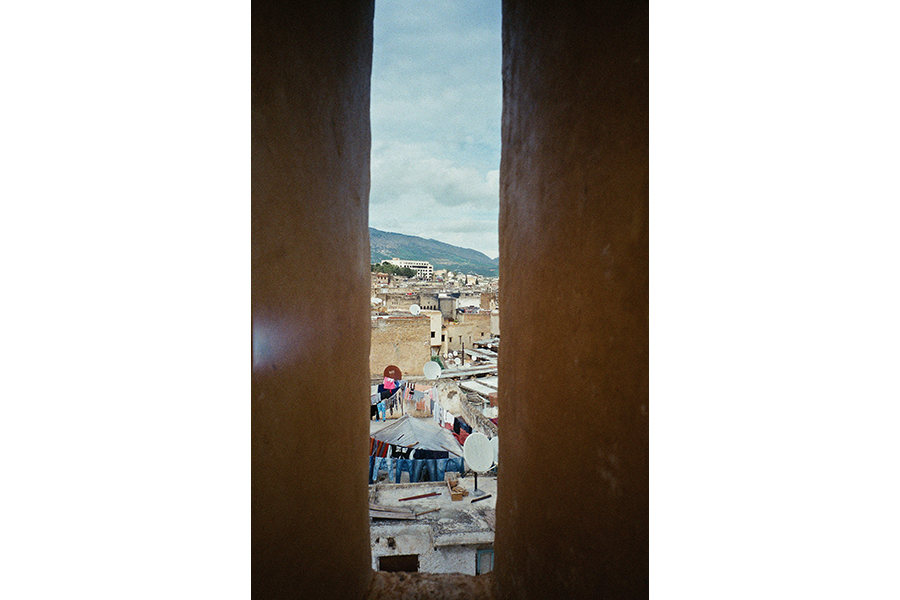 A slice of a town as seen though a narrow window: cloudy blue sky, hills, and the roves of white and beige buildings