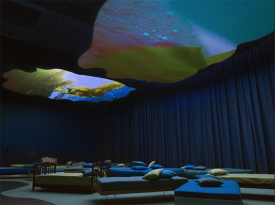 A room filled with beds with underwater scenes projected on the ceiling.