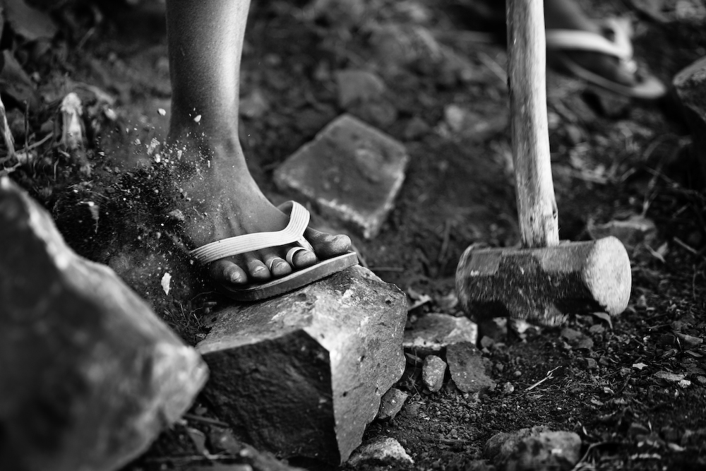 Mallet hitting a rock held down by a foot (in black and white).