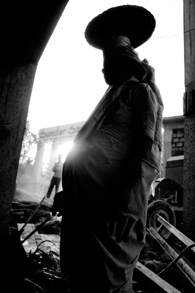 Pregnant woman standing in an archway with the sun shining off her baby bump (in black and white).