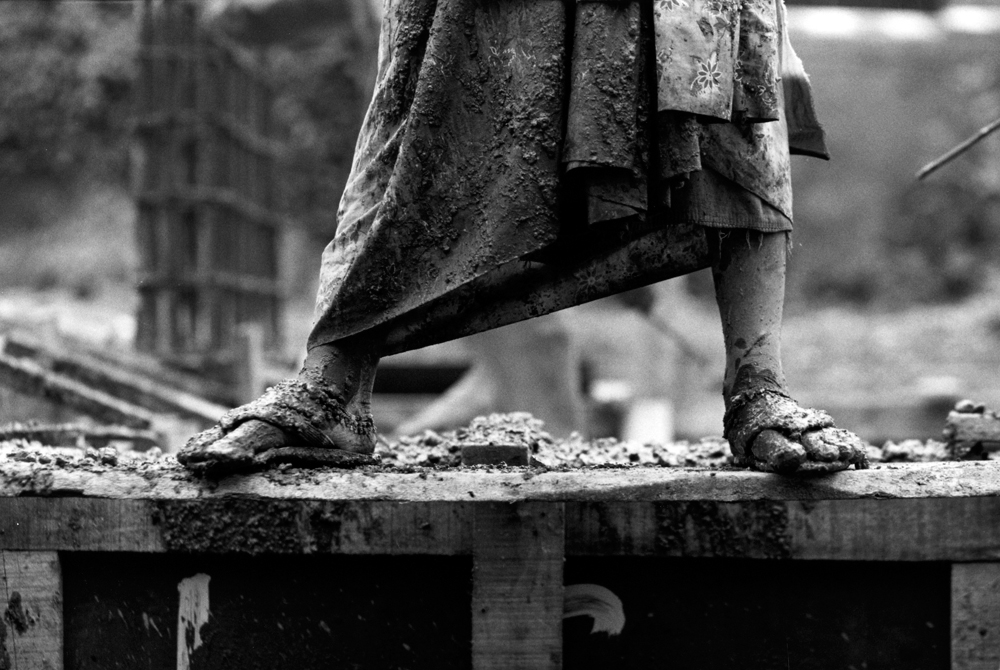 Muddy feet of a person wearing sandals standing on a dock (in black and white).