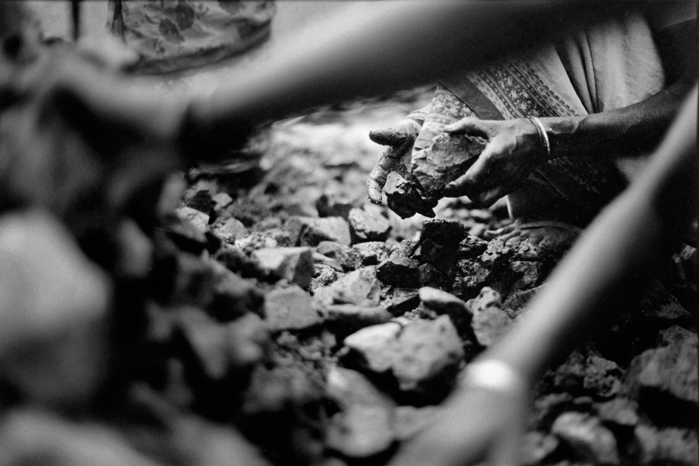 Close-up of the hands of people inspecting a pile of rocks (in black and white).