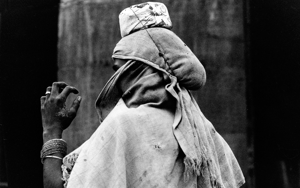 Back of the head of a person carrying a something wrapped in cloth on their head (in black and white).