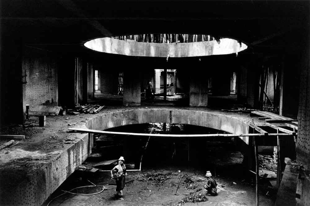 Construction site and workers in an underground structure (in black and white).