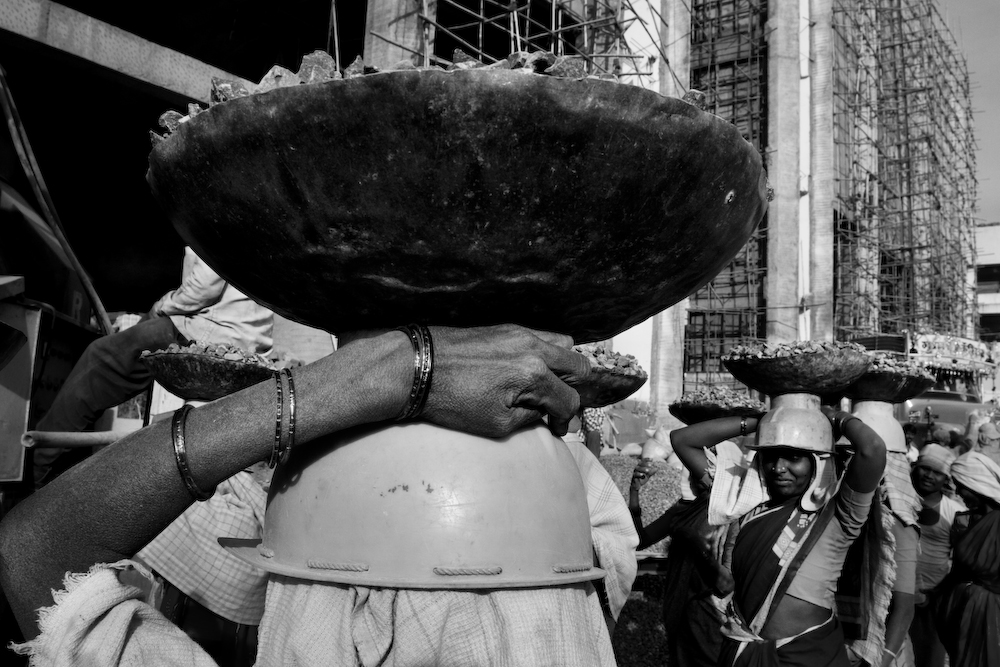 Head, arm and basket up close of woman holding a basket on her head in a line of women (in black and white).