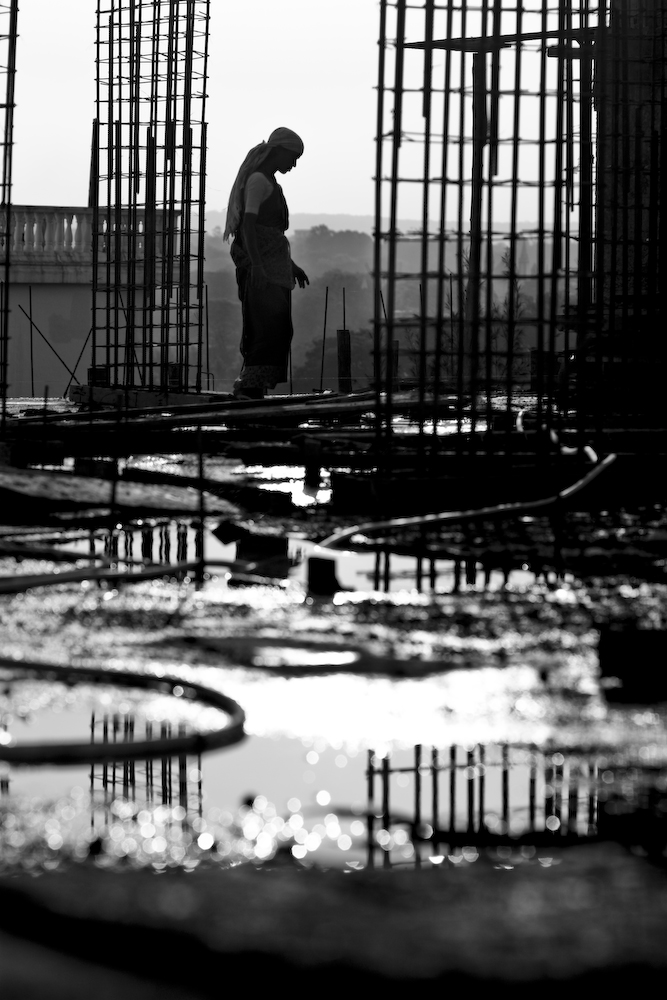 Construction site ground with a person's legs in the distance (in black and white).