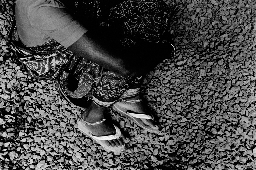 Body and feet of someone curled up on pebbled ground  (in black and white).