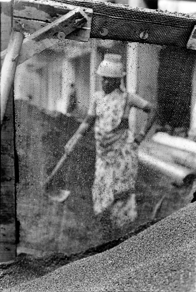 Screen in focus with a person holding an ax behind the screen, out of focus (in black and white).