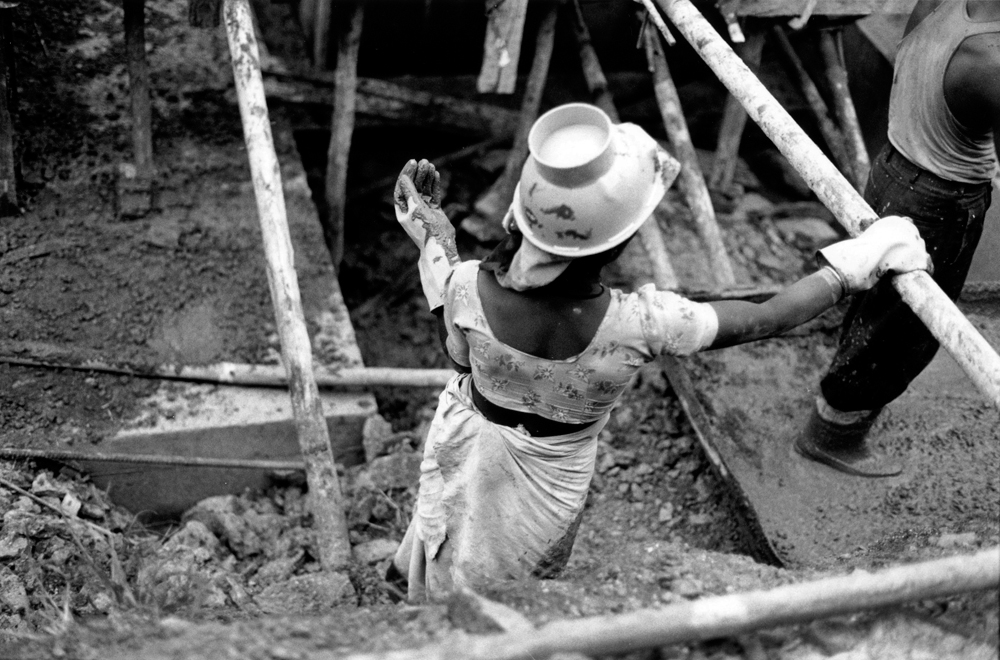 Worker with a bucket hat and large gloves working on a construction site (in black and white).