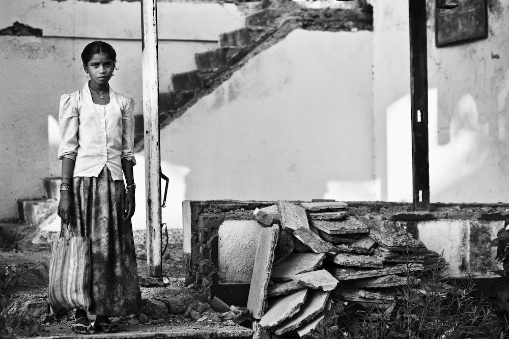 Young girl looking on next to a pile of slate rocks (in black and white).