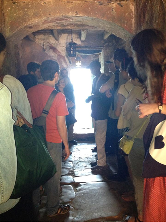Tourists standing in a cave-like doorway.