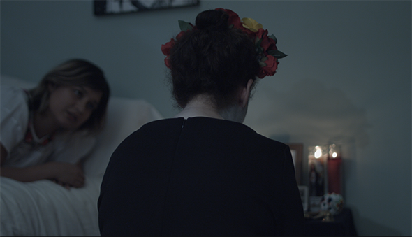 "Still from ""Muerte,"" figure seated at bedside"