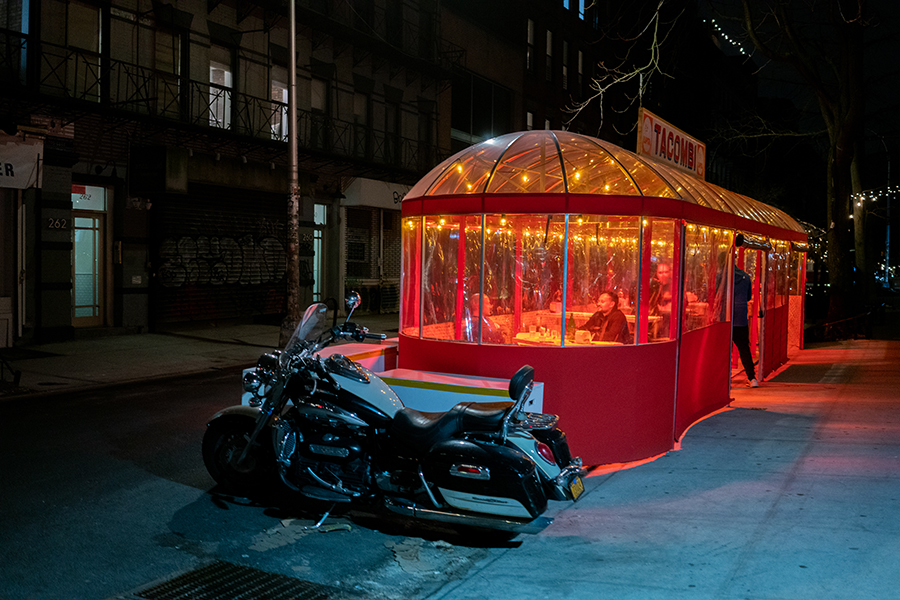 A motorbike leans next to the foodshed of a Mexican restaurant where two men dine inside.