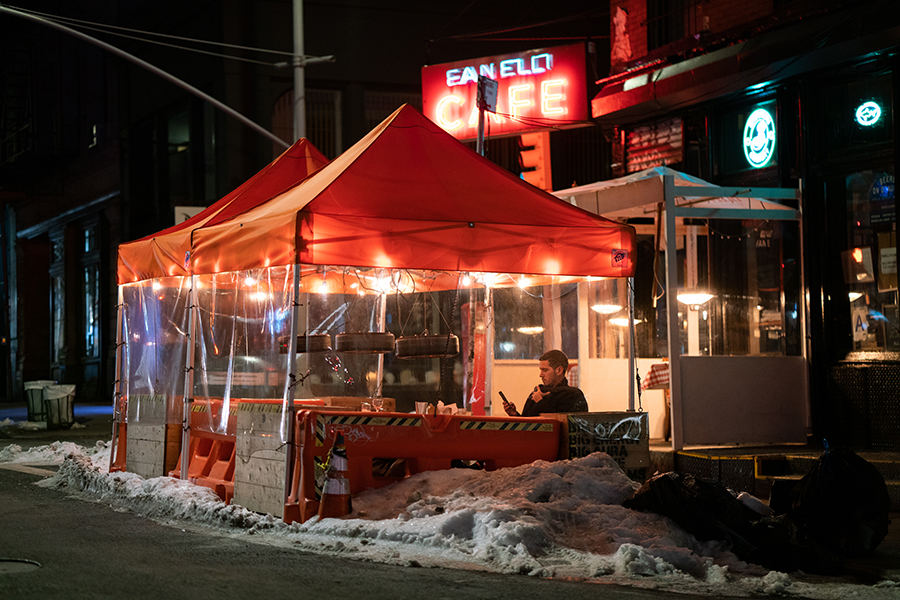 Man is seated alone at Fanelli's Cafe during a winter storm.