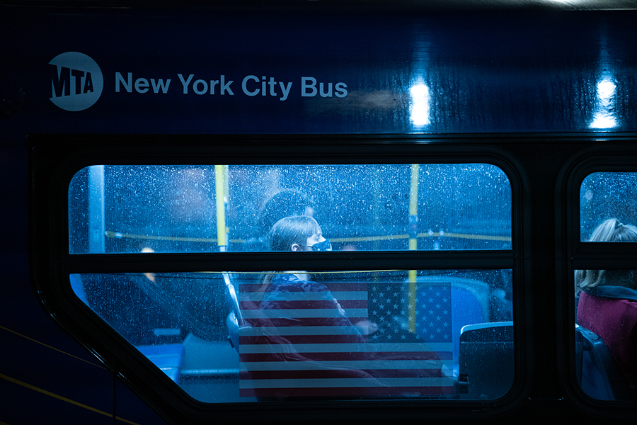 Masked woman on a bus; she looks forward above an American flag printed on the bus's side.