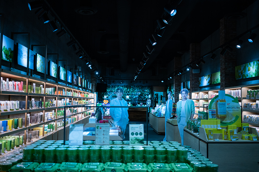 The interior of a health store; a group of cardboard cutouts stares back inside the store.