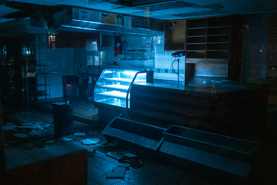 The dilapidated inside of a nondescript shop where one singular display case is still lit.