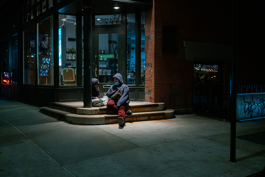 Man and a woman enjoy a conversation under a closed storefront entrance.