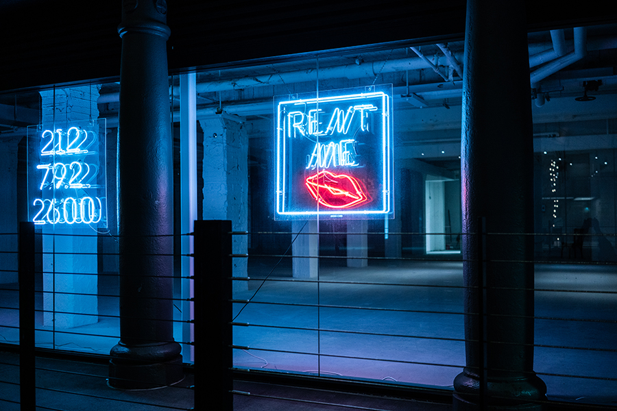 """A neon sign reads """"rent me"""" in front of a vacant gallery space in Chelsea."""