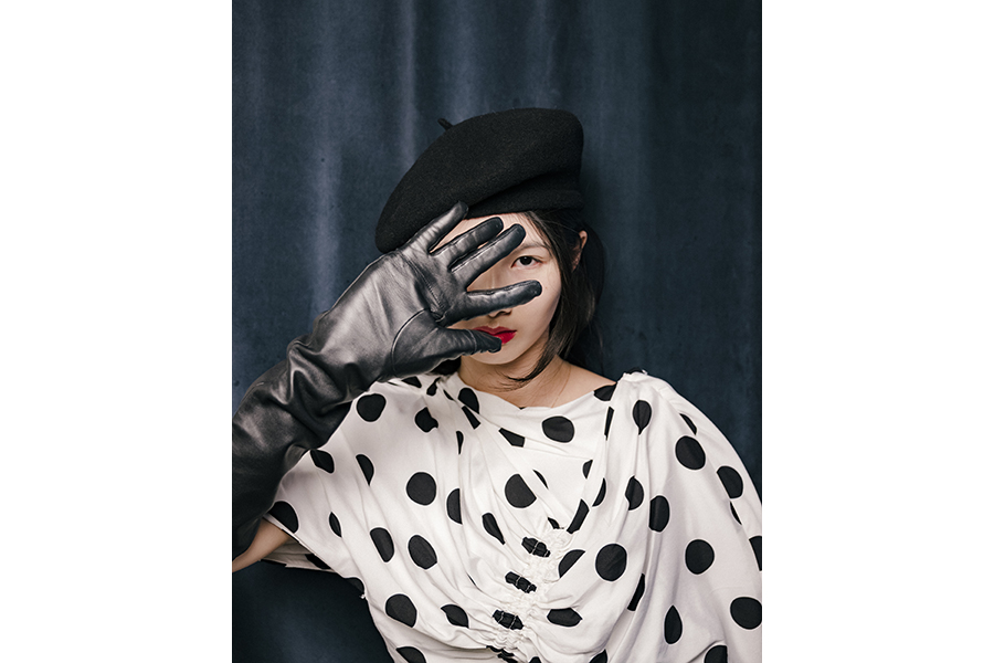 A woman in black-on-white polka-dot-shirt, a black beret, red lipstick, holds a black-leather-gloved left hand in front of her face, peering through her fingers