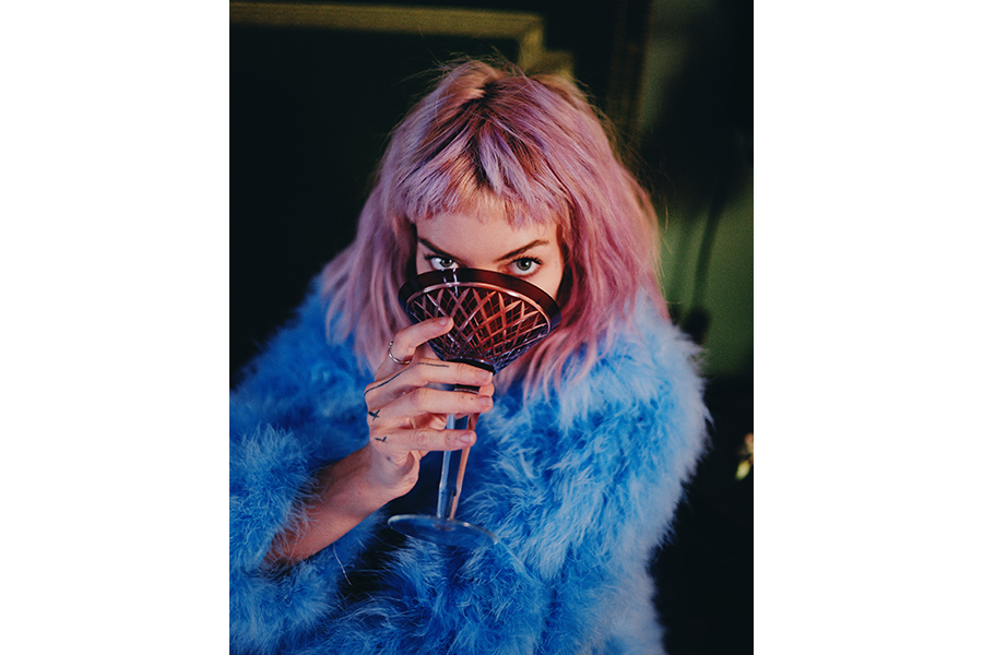 A woman in a blue shag coat sips from a large, purple-red, etched martini glass, partially obscuring her face, but looking up to meet the camera's gaze
