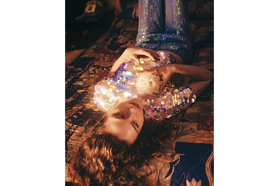A woman in a sequined shirt lies back on a patterned bedspread, one hand on her heart one on her stomach