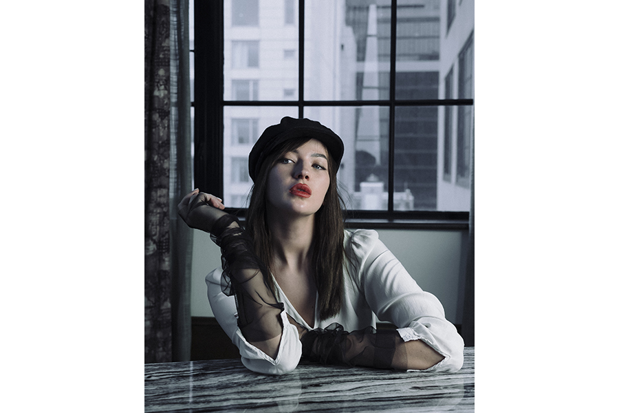 A woman seated at a table before a window, with highrise buildings in the background, leans one arm on the table and rests the other elbow; she wears black mesh-lace fingerless gloves, a white button-down, a black beret, and red lipstick