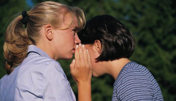 Woman whispering in another woman's ear.