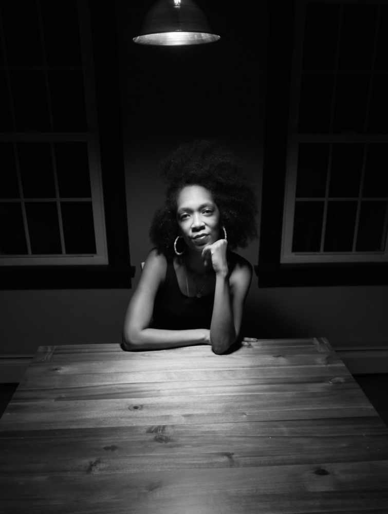 Shatima Jones sits at a table posed with a loose fist under her chin.